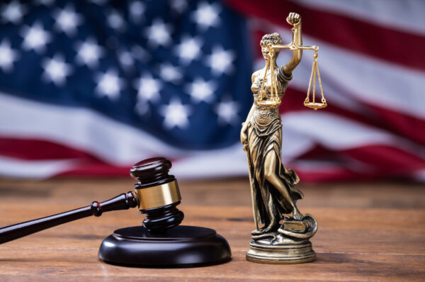 Wooden Gavel With Golden Scales On Table In Front Of US Flag